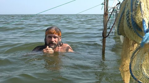 Mature male fisherman in kerchief with beard dives into water to repair fishing nets in ocean. Fishing nets are dried in open sea near shore with a small storm