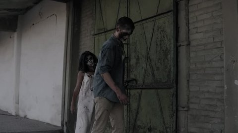 Two zombies are walking with an abandoned house on the background. Brunette girl with wounded face and bloody white dress and wounded male zombie are walking outdoors. Accelerating footage