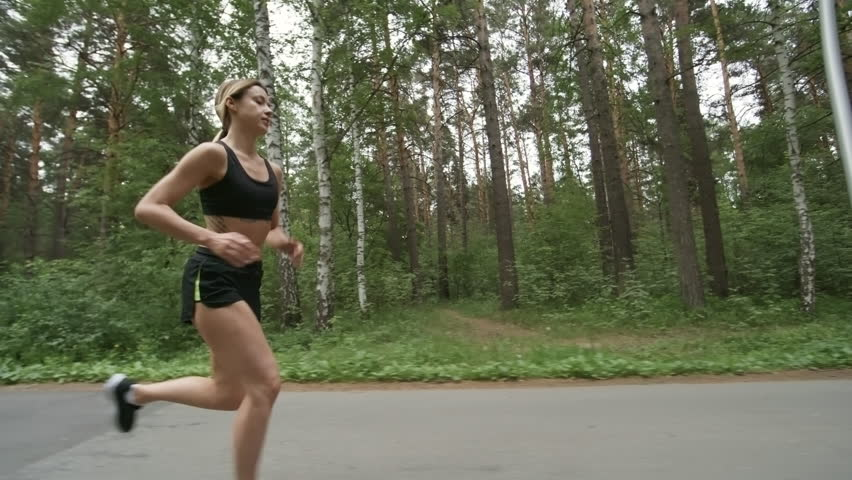 Tracking shot of sporty young woman with fit body running along forest road in morning   Shutterstock HD Video #1016970343