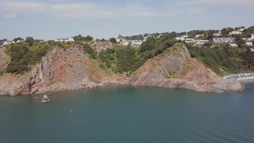 Flying towards cliff formations in Torquay, Devon in England.