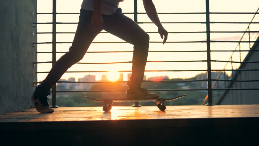 Man starts riding a skateboard on a city background, slow motion. | Shutterstock HD Video #1016984383
