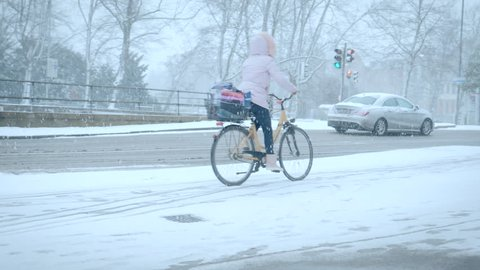 LUBECK, GERMANY - FEBRUARY 11, 2018: Cyclists in the winter city, riding bike on snow covered road