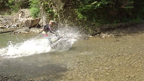 Motocross in the wild. The rider crosses the small river. Splashes in the sun. Slow motion