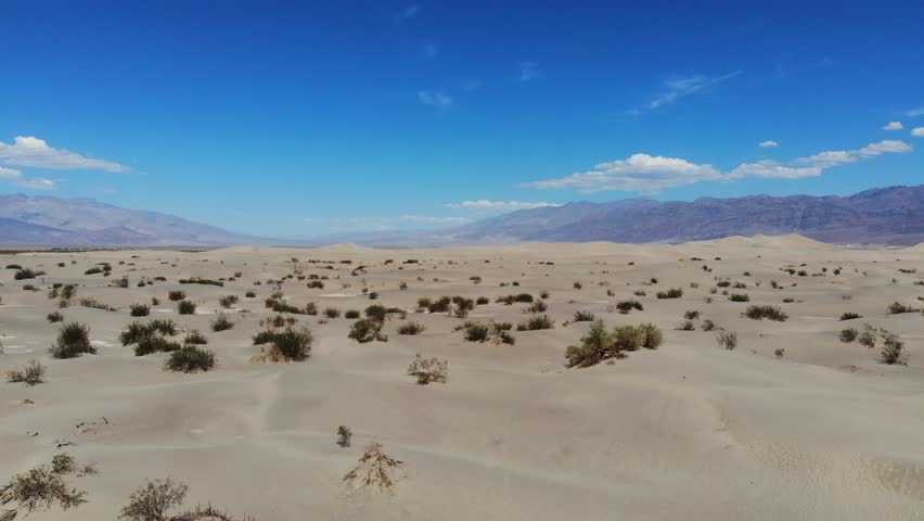 Drone Views Flying Across Mojave Desert, White Desert Sand Below and Mountains On Horizon, Perfect Nature Scene  | Shutterstock HD Video #1016993953