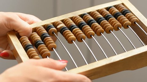 A girl is holding a vintage wooden abacus, performs a calculation on counter. Close-up.