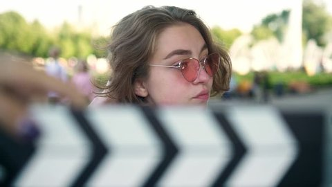 Cute young actress with short wavy fair hair in white t shirt and pink sunglasses smiling to camera and touching her hair after clapperboard being used. Advetisement. Slider slow motion portrait shot