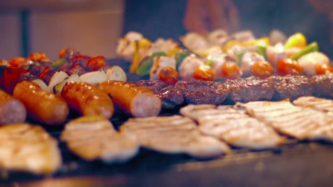 FullHD video - Local. Turkish street vendor turns kabobs. sausages. hamburgers and chicken breasts on a barbecue grill in preparation for a busy afternoon rush.