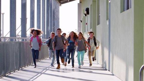 Elementary school kids running to camera in school corridor