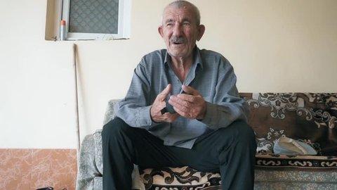 Senior man sitting on couch. Closeup shot. Still camera