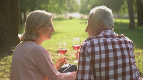Merry senior couple sitting on grass in park and drinking wine, celebrating date
