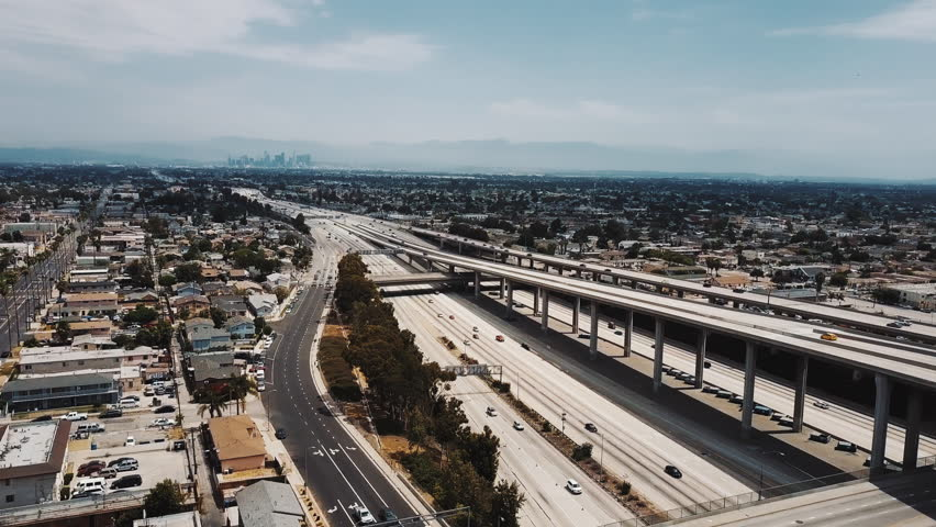 Drone panning right over amazing American city and big highway junction interchange with cars on multiple road levels. | Shutterstock HD Video #1017108583