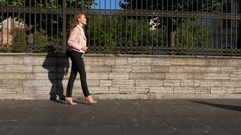 Young woman wearing high heels walkin on street. Full length portrait, slow motion