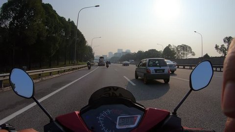 Hyper lapse riding a motorcycle in the morning haze at the highway,through to heavy traffic. First-person view. Point of view.