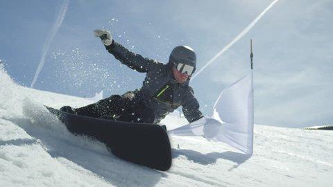 SLOW MOTION CLOSE UP: Racing snowboarder riding slalom between gates