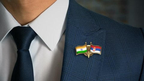 Businessman Walking Towards Camera With Friend Country Flags Pin India - Serbia