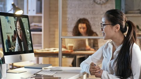 Young asian business lady in eyeglasses talking with female colleague via video call on computer while working late in the office