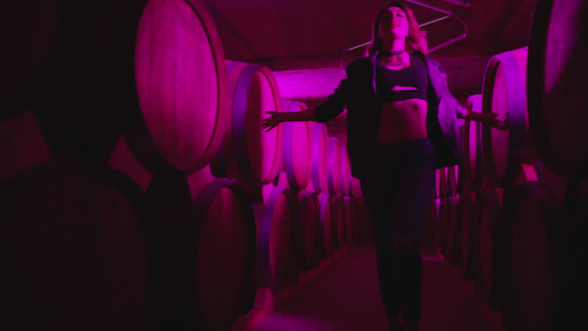 Hot girl dancing . Dances with real strobe lights in colorful light winery with brandy , whiskey or wine barrels . Sexy body posing in wine house .  | Shutterstock HD Video #1017234103