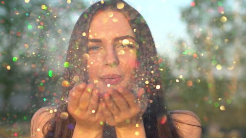 Beautiful woman blowing confetti in slow motion on nature beach. Caucasian happy teenage model girl blowing gold glitter off hands in summer park at sunset. Simmertime Outside Beauty happiness summer