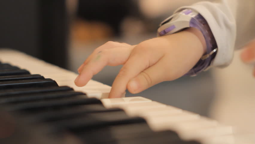Close up of two child's small hands playing piano