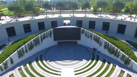 Aerial view: drone fly from Amphitheater boy with dad by hand go to cinema park. Aerial footage cityscape Kuban summer. Beautiful view park Krasnodar.
