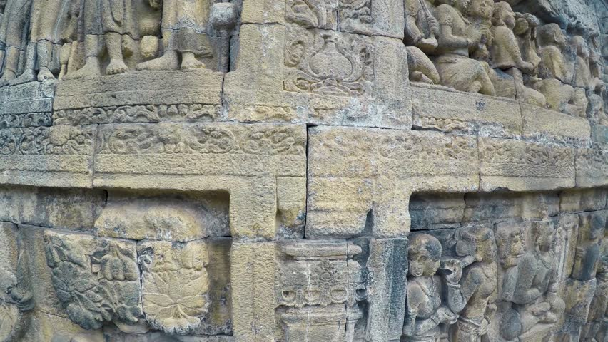 Close up view of Borobudur Temple Walls.Close-up of gorgeous reliefs narrating Buddhist scriptures and adorning stone facades of Borobudur temple.