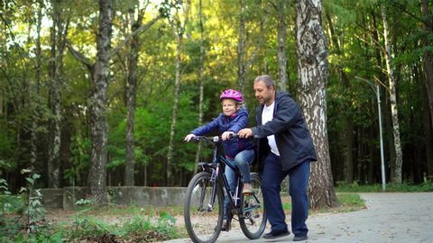 Father teaching daughter to ride bike at urban park. Child girl learning biking with the dad's help.Family and childhood concept.Sunny autumn day.