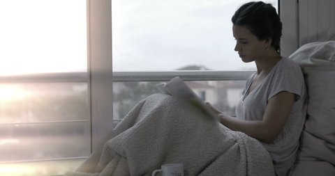 Woman reading in bed and drinking coffee – 4k