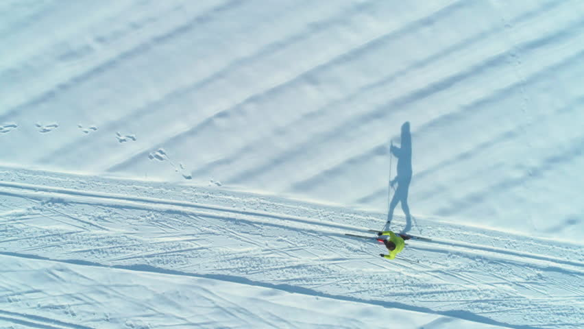 AERIAL, TOP DOWN: Flying above energetic woman skiing down the narrow trails on a sunny day. Cinematic shot of active female tourist cross country skiing during fun winter holiday in scenic Slovenia.