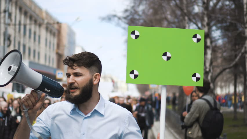 Angry adult young man with a banner in hands go and shouts loudspeaker rally. Aggressive protester on strike. Revolution in city during day. Crowd people in the background on street. 20s caucasion boy | Shutterstock HD Video #1017372403