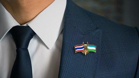 Businessman Walking Towards Camera With Friend Country Flags Pin Thailand - Uzbekistan
