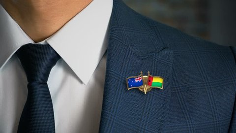 Businessman Walking Towards Camera With Friend Country Flags Pin New Zealand - Guinea-Bissau