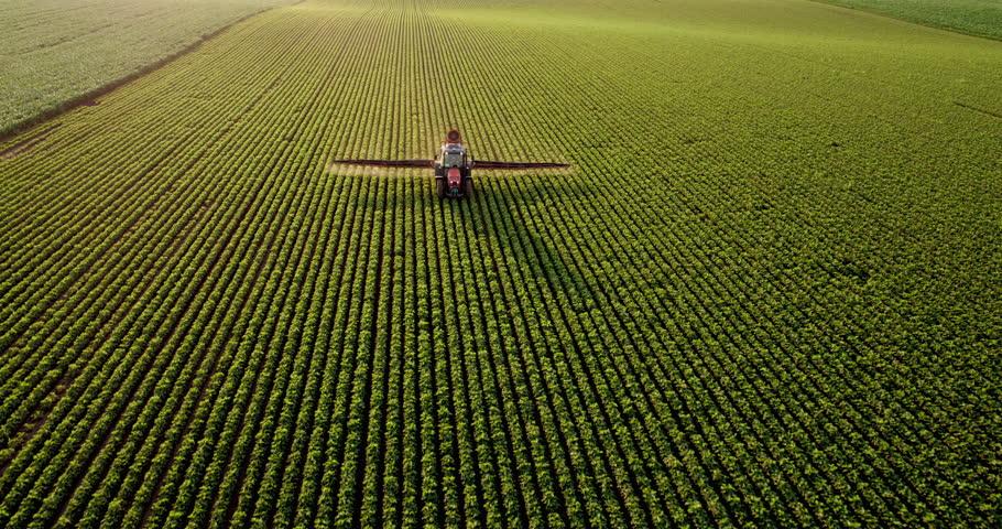 Aerial drone shot of a farmer spraying soybean fields #1017454063