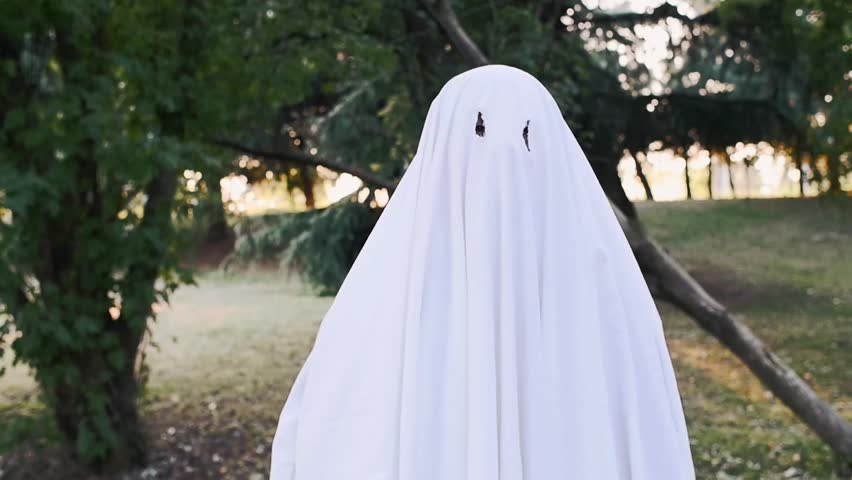 father and son playing ghosts with sheets in the garden. Video halloween concept