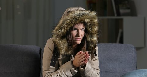 Angry woman warmly clothed in a cold home sitting on a couch in the night