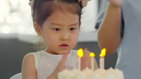 Handheld medium shot of adorable Asian girl in party hat clapping and staring at birthday cake with lit candles