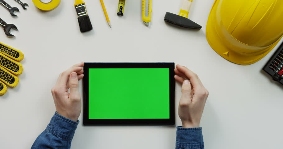 Close up of the white table with building instruments on which man's Caucasian hands scrolling and tapping on the black horizontal tablet computer with green screen. Top view. Flat lay. | Shutterstock HD Video #1017586783