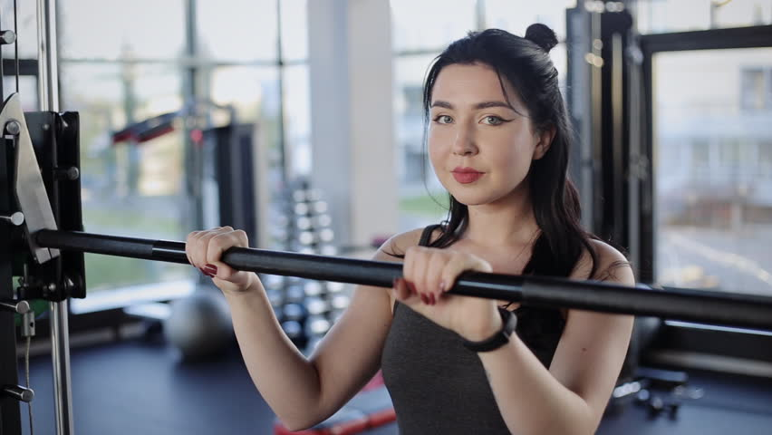 Portrait of young woman at the gym using fitness equipment. Female fitness girl looking at camera | Shutterstock HD Video #1017654343