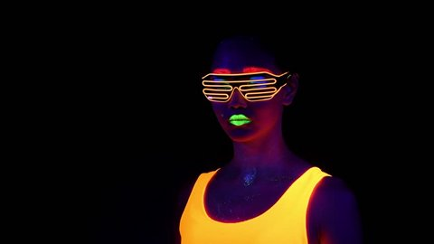 Beautiful sexy woman with UV face paint, glowing clothing, glowing bracelet, glasses in front of camera, half body shot. Asian woman. Party concept.