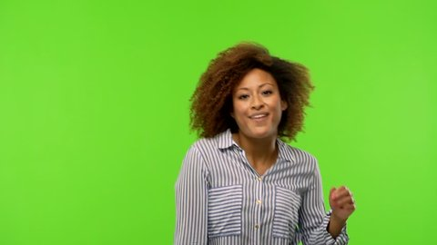 young afro american woman dancing on a green screen chroma key background