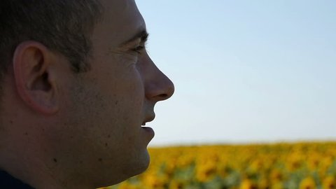The face of a male farmer close-up looks at the sunflower field. Young promising farmer cares about the future harvest.