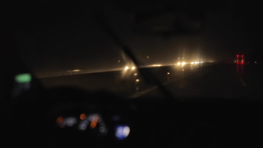 Driving a car on freeway at night in rain. Working windshield wipers. Interior of a car. Speedometer | Shutterstock HD Video #1017769363