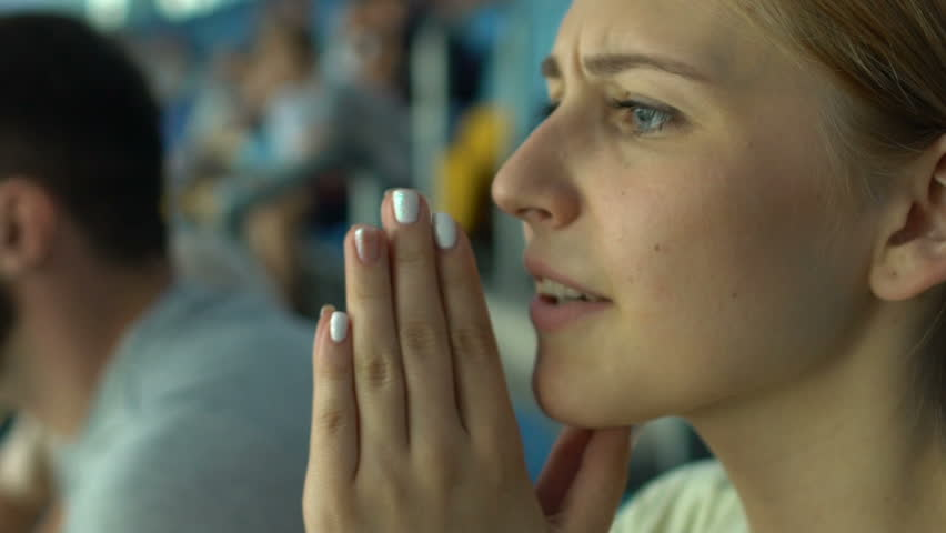 Girl fan worries about sport game or races, praying superstitious, face closeup