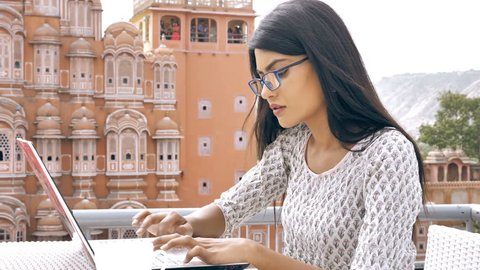 An attractive and focused girl in kurta working on a laptop on an important assignment or project. A movement shot  of beautiful and busy businesswoman typing on a laptop keyboard in exterior setup