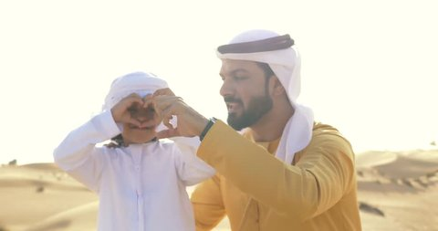 Father and son playing together in the desert. Family doing a safari in Dubai