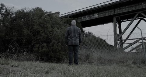 Creepy man wearing white halloween mask turns then stands with head tilted in scary manner in front of bushes and old railway bridge