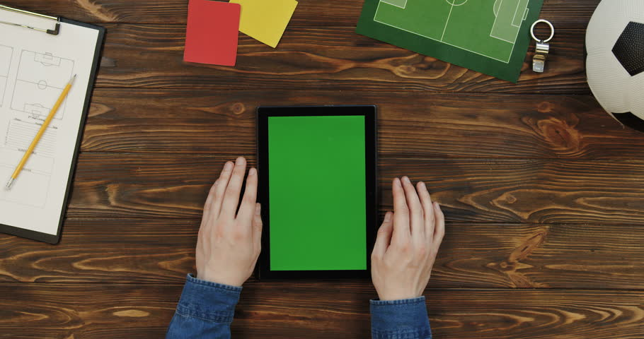 Top view on the black tablet device lying vertically on the wooden table with football fan things on it and male hands scrolling and taping on the green screen of it. Chroma key.   Shutterstock HD Video #1017874483