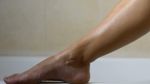 Woman applying lotion after waxing legs in bathroom, hair removal and skin care