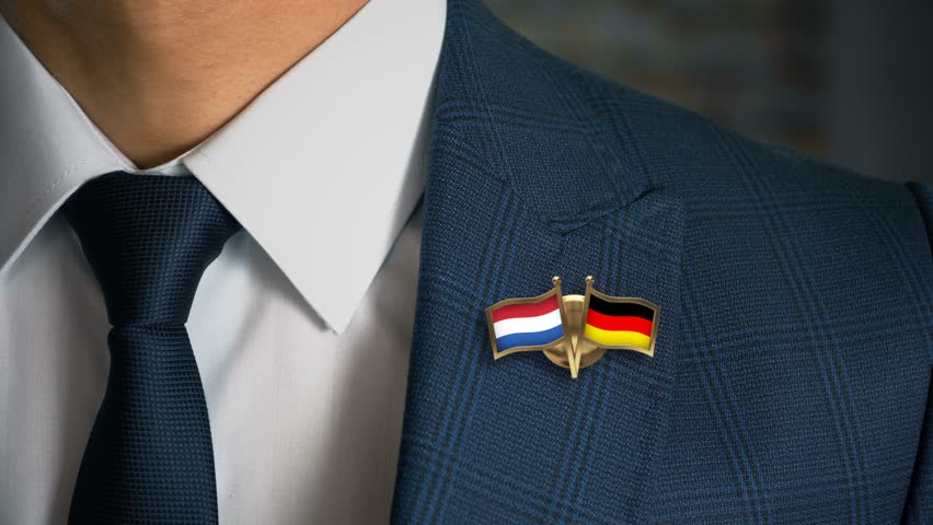 Businessman Walking Towards Camera With Friend Country Flags Pin Netherlands - Germany | Shutterstock HD Video #1017908203