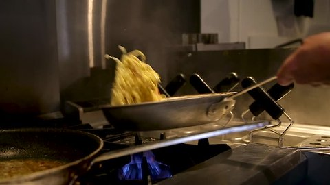 Fresh pasta being cooked in a pan in a restaurant kitchen.