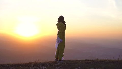 portrait of a beautiful girl in hijab at sunset in the mountains